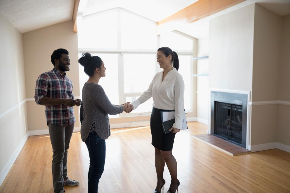 Real estate agent showing young couple a home